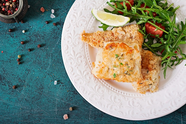 Filetes de pescado blanco frito y ensalada de tomate con rúcula. vista superior