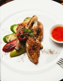 Filetes de pollo a la parrilla, asados y verduras en un plato blanco con salsa