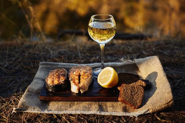 Filetes de salmón cocido e ingredientes en una tabla de madera vieja