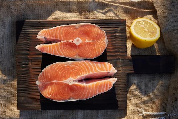 Filetes de salmón crudo e ingredientes en una tabla de madera vieja