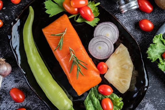 Filetes de salmón crudo, pimienta, kiwi, piña y romero en un plato y piso de cemento negro.