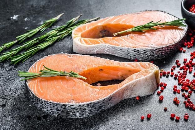 Filetes de salmón con romero y pimienta rosa. pescado orgánico crudo. espacio negro. vista superior