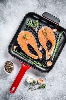 Filetes de salmón con romero y pimienta en una sartén. pescado orgánico crudo. espacio gris. vista superior