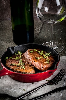 Filetes de ternera a la parrilla caseros en una sartén en porciones, con un tenedor, cuchillo y una copa de vino en la mesa de piedra negra