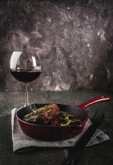 Filetes de ternera a la parrilla caseros con tomillo en una sartén en porciones, con un tenedor, cuchillo y una copa de vino