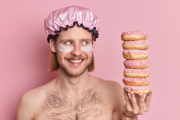 Filmación en interiores de alegre joven europeo sonríe ampliamente mira el montón de deliciosas donas tiene la tentación de comer postres dulces posa en topless