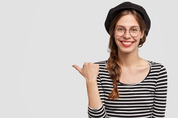 Filmación en interiores de amable mujer parisina con amplia sonrisa, puntos a la izquierda
