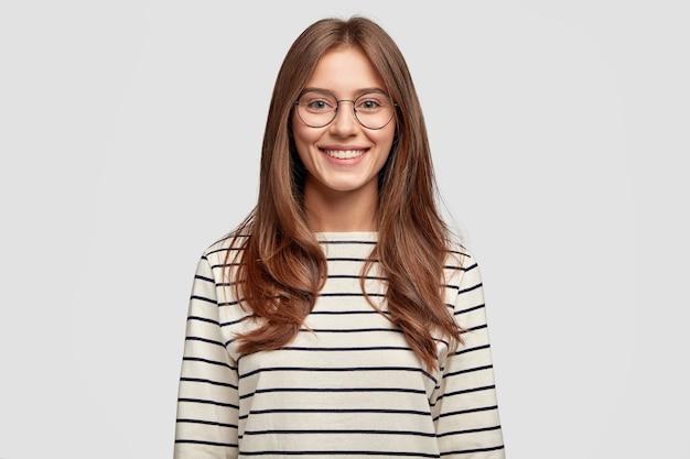 Filmación en interiores de una atractiva joven con gafas posando contra la pared blanca