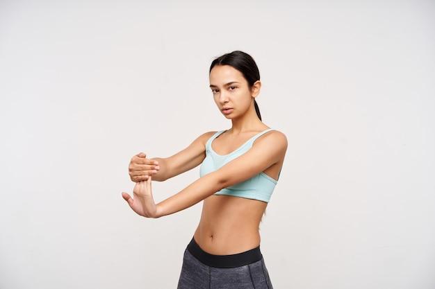 Filmación en interiores de una atractiva joven mujer de cabello castaño tirando de sus dedos mientras estira las músculos y mira con atención al frente, aislado sobre una pared blanca