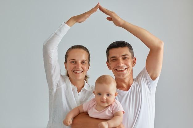 Filmación en interiores de familia positiva feliz posando fondo claro aislado, mirando a la cámara, sosteniendo al bebé en las manos, mamá y papá haciendo la figura del techo con las manos y los brazos por encima de la cabeza, seguridad.