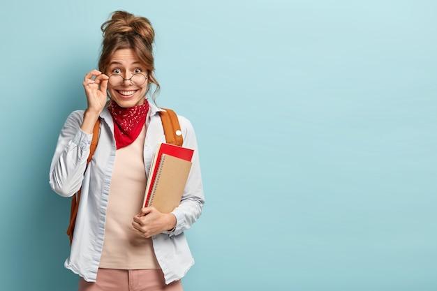Filmación en interiores de feliz apuesto joven estudiante universitario lleva gafas redondas ópticas