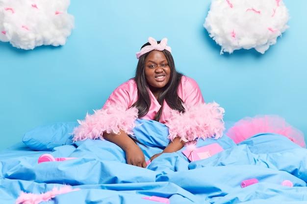 Filmación en interiores de feliz hermosa dama afroamericana obesa disfruta de un ambiente doméstico viste bata tiene uñas largas pasa tiempo libre en la cama aislado en azul