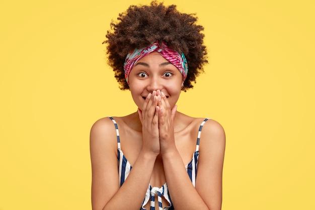 Filmación en interiores de feliz mujer de piel oscura encantada mira con alegría