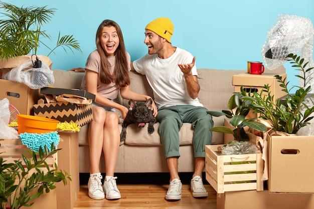 Filmación en interiores de la feliz pareja joven sentada en el sofá rodeado de cajas