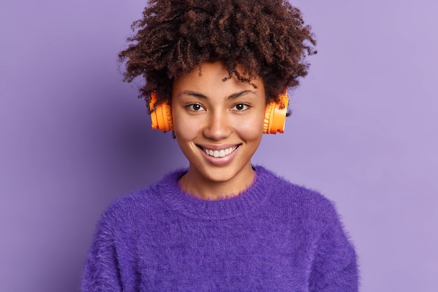 Filmación en interiores de una hermosa adolescente sonríe felizmente lleva auriculares estéreo escucha música de la lista de reproducción vestida con un cálido jersey de cachemira