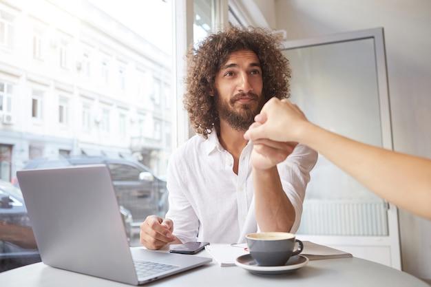 Filmación en interiores de un hombre barbudo joven encantador con el pelo largo y rizado sentado junto a la ventana en la cafetería, trabajando fuera de la oficina con el portátil, saludando con la mano femenina