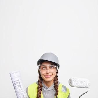 Filmación en interiores de la ingeniera mujer complacida sostiene el rodillo de pintura y el plano de papel se ve por encima de las obras en el sitio de construcción