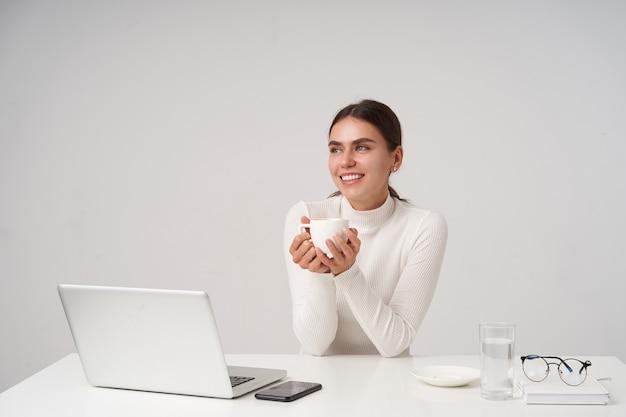 Filmación en interiores de joven mujer morena atractiva positiva en ropa formal tomando una taza de café mientras trabajaba en la oficina con su computadora portátil, aislado sobre una pared blanca