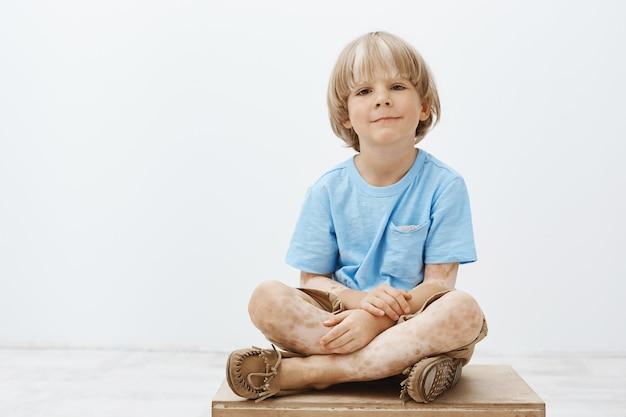 Filmación en interiores de lindo niño rubio feliz con sonrisa positiva sentado con las manos cruzadas, con vitiligo, sonriendo ampliamente mientras pasa el rato con amigos en el jardín de infantes