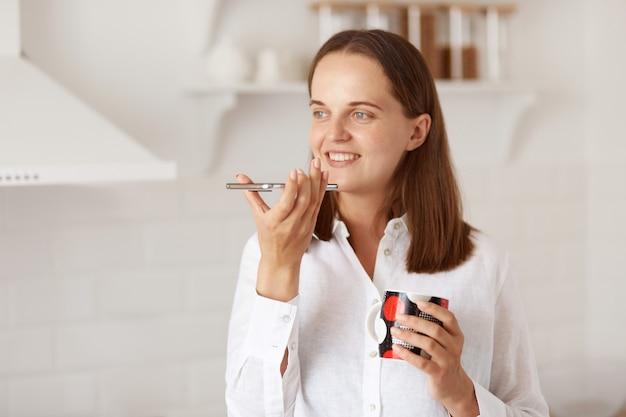 Filmación en interiores de una mujer adulta joven atractiva que hace un mensaje de voz con un teléfono inteligente mientras se relaja en casa y bebe té o café caliente, de pie en la cocina ligera.