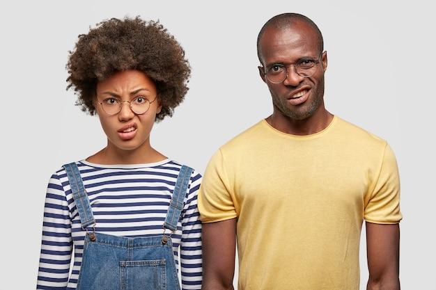 Filmación en interiores de una mujer afroamericana con cabello rizado y nítido, un hombre calvo muy cerca el uno del otro, siente aversión al ver algo desagradable aislado en la pared blanca. expresiones faciales negativas.