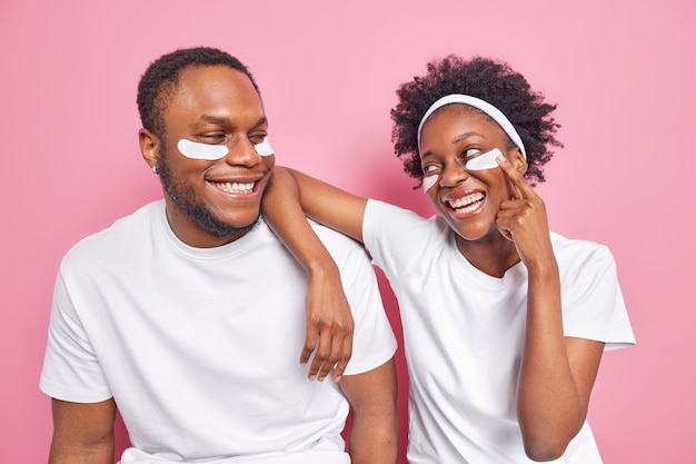 Filmación en interiores de la mujer y el hombre negros despreocupados felices miran con una sonrisa el uno al otro aplicar parches de belleza