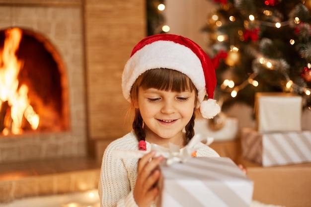 Filmación en interiores de niña feliz positiva con suéter blanco y sombrero de santa claus, sosteniendo la caja actual en las manos, posando en la sala festiva con chimenea y árbol de navidad.
