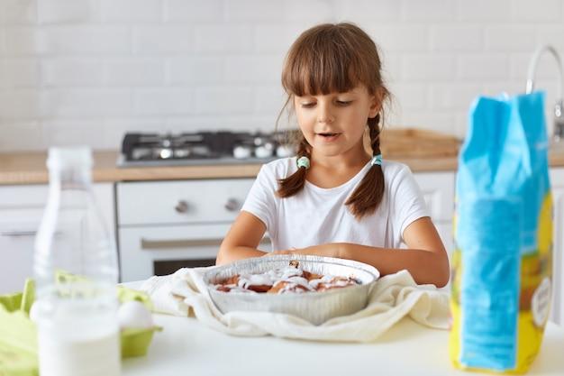 Filmación en interiores de la niña linda en la cocina mirando la galleta en la mesa, estando lista para probarla, niña curiosa con coletas lindas con camiseta blanca posando en casa.