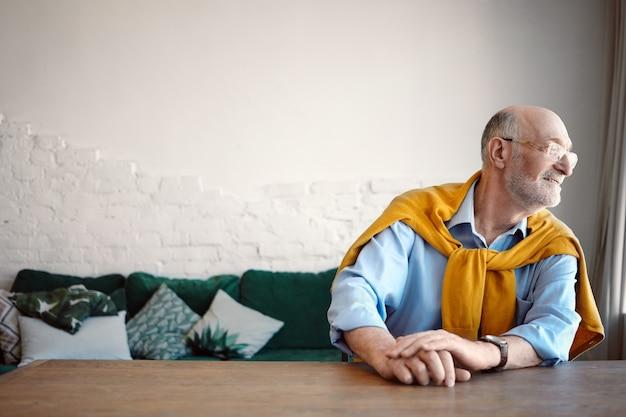 Filmación en interiores de psicólogo masculino senior caucásico barbudo de pelo gris de moda en camisa azul y gafas sentado en el escritorio en la oficina en casa y mirando por la ventana mientras espera al cliente.