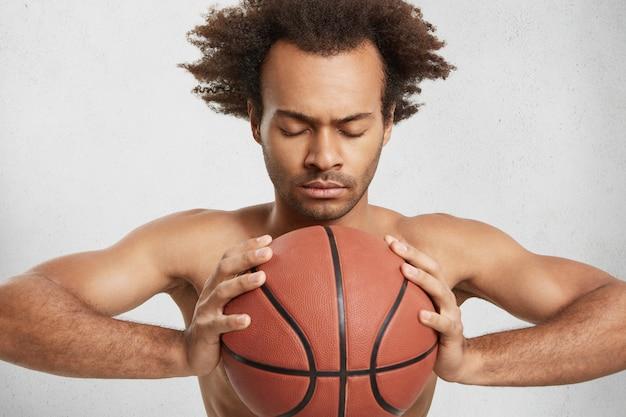 Filmación en interiores de serio jugador de baloncesto concentrado con balón se prepara solo para un partido importante