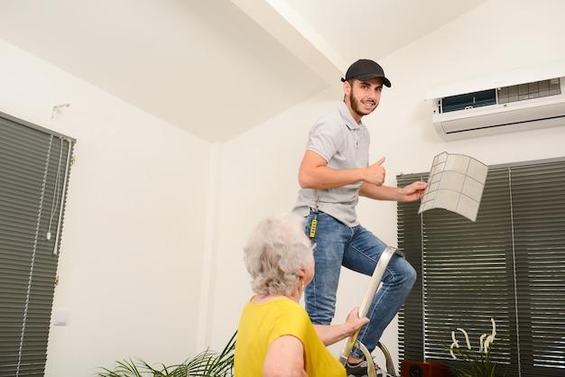 Filtro de aire de limpieza de electricista joven guapo en una unidad interior del sistema de aire acondicionado en una casa de cliente con una mujer mayor