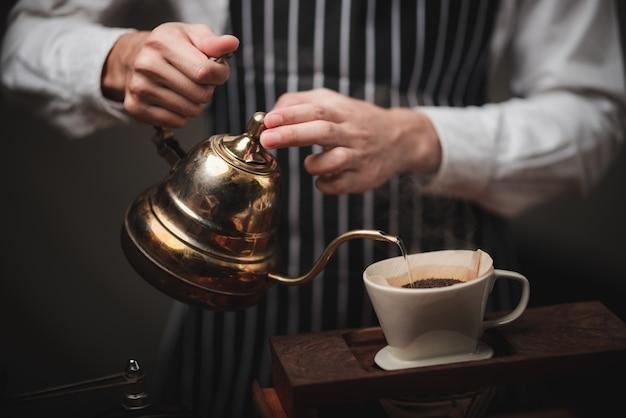 Filtro de café de goteo manual, barista vertiendo agua caliente en el café molido tostado con filtro