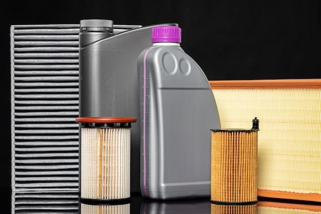 Filtros de aceite de coche y aceite de motor pueden sobre fondo oscuro, de cerca.
