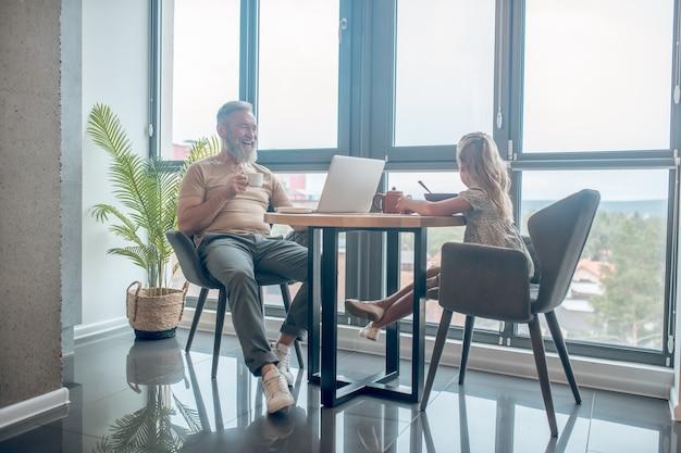 Fin de semana familiar. un hombre y su hija sentados a la mesa, el hombre que trabaja, su hija comiendo