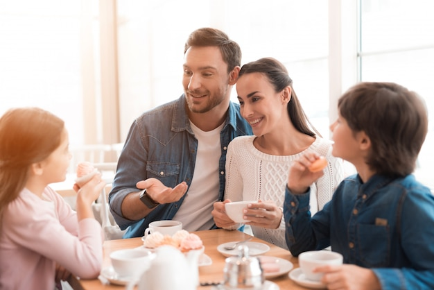 Fin de semana por la mañana de amorosa familia feliz en el café.