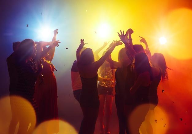 Fin de semana. una multitud de personas en silueta levanta sus manos en la pista de baile sobre fondo de luz de neón. vida nocturna, club, música, baile, movimiento, juventud. colores amarillo-azul y niñas y niños en movimiento.