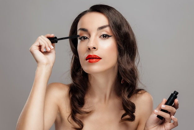 Fina mujer morena con lápiz labial rojo en los labios.