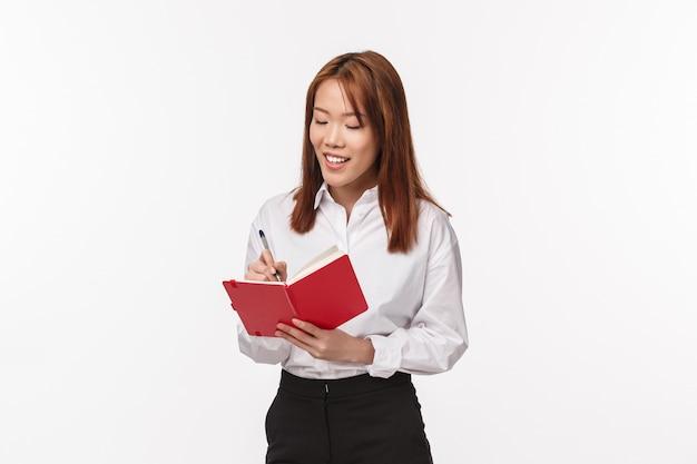 Finanzas, mujeres y concepto de negocio. exitosa joven dama asiática de la oficina trabajando en el proyecto, escribiendo en el cuaderno, mira el diario con una sonrisa de satisfacción, creando un horario,
