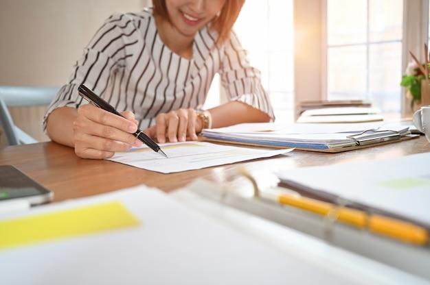 Las finanzas del negocio y el concepto de contabilidad, la empresaria que señala el gráfico y la tabla al uso del análisis para los planes mejoran calidad.