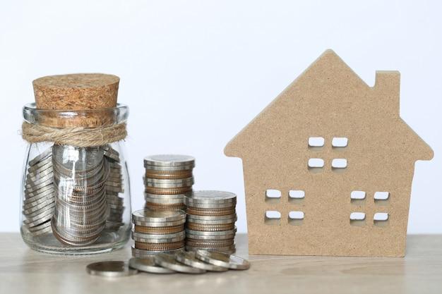 Finanzas, pila de monedas, dinero y casa modelo sobre fondo blanco, inversión empresarial y bienes raíces