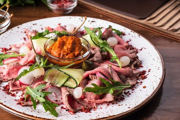 Finas rodajas de rosbif con rúcula, rábano y cebolla marinada.