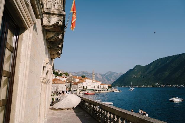 Fineart boda foto en montenegro perast una pareja de novios en la terraza del hotel con panorámica