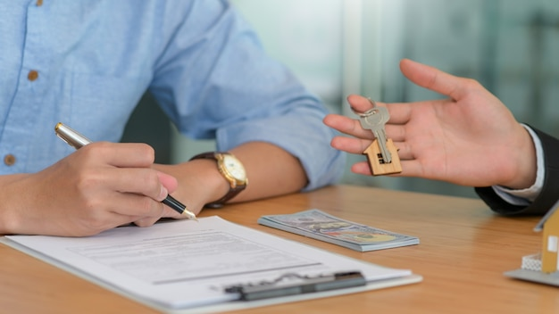Firma de contrato y entrega de llaves de casa para compraventa de viviendas.