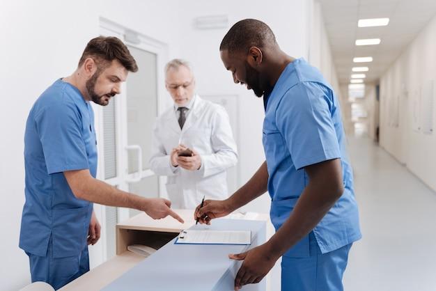 Firma de documento importante. doctores diligentes calificados alegres que trabajan en el hospital y discuten el diagnóstico del paciente mientras un colega anciano usa el teléfono en el fondo