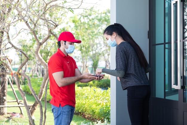 Firma de la firma en el dispositivo de teléfono inteligente para obtener un paquete. mujer que recibe el paquete del repartidor en uniforme rojo