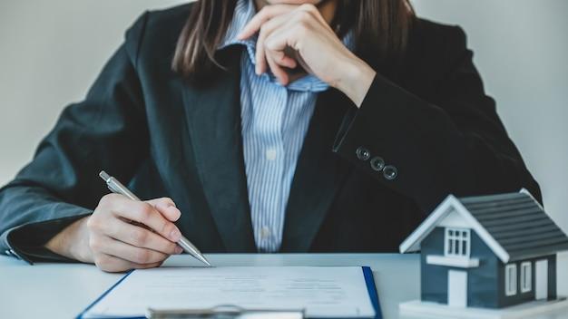 Firma manual del contrato después de que el agente de bienes raíces explica al comprador el contrato comercial, el alquiler, la compra, la hipoteca, el préstamo o el seguro del hogar.