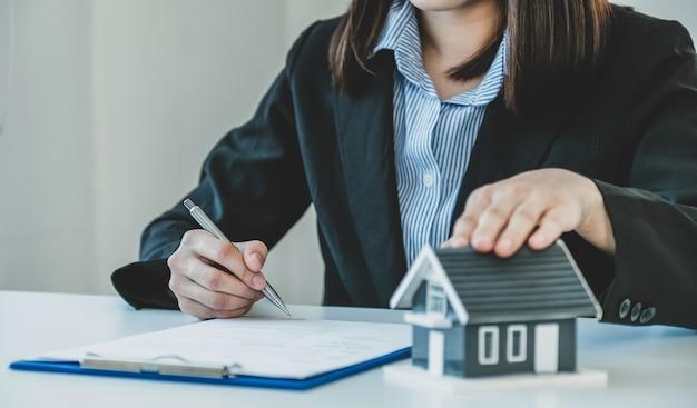 Firma manual del contrato después de que el agente de bienes raíces explica el contrato comercial al comprador.