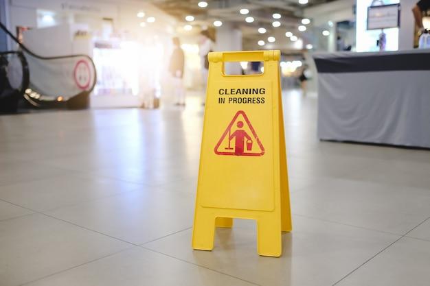 Firmar mostrando advertencia de precaución piso mojado en el aeropuerto.