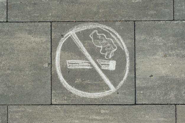 Firmar no fumar pintado en la acera gris