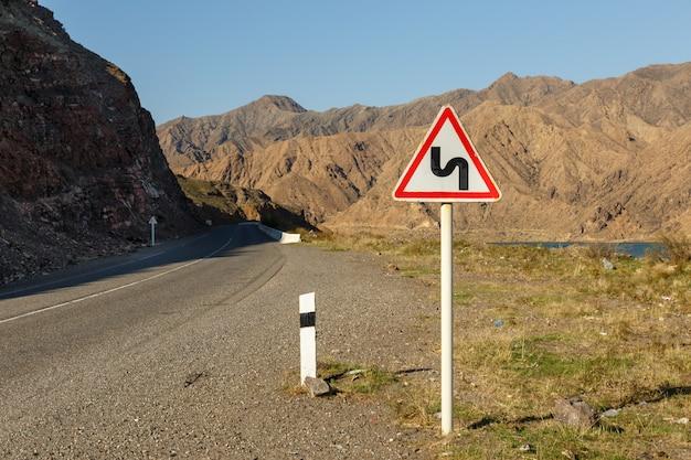 Firmar sinuoso camino en una carretera de montaña, advertencia señal de tráfico kirguistán